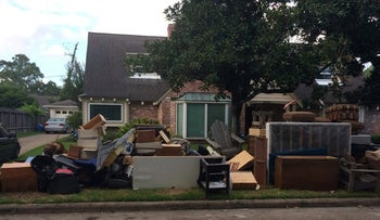 Exterior of the Lewis family home, debris piled at the curb, in the Jewish neighborhood of Meyerland, Houston.