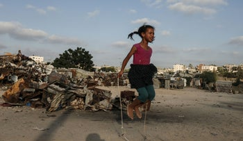 A Palestinian child plays in an impoverished neighborhood of the Khan Younis refugee camp, southern Gaza, August 25, 2018.