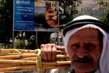 A Palestinian man walks near a billboard describing now-suspended USAID infrastructure funding in the village of al-Badhan, north of Nablus in the West Bank. August 25, 2018