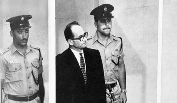 Adolf Eichmann standing in his glass cage, flanked by guards, in a Jerusalem courtroom during his trial in 1961.