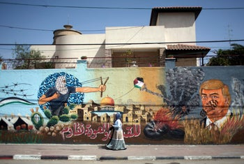 """Palestinian women walk next to graffiti showing U.S. President Donald Trump with a footprint on his face and Arabic that reads, """"For al-Quds (Jerusalem) and the right of return we resist."""" Gaza City, May 20, 2018"""