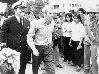 File photo: U.S. Navy Lt. Cmdr. John McCain, center, is escorted by Lt. Cmdr. Jay Coupe Jr., to Hanoi, Vietnam's Gia Lam Airport, after McCain was released from captivity on March 14, 1973.