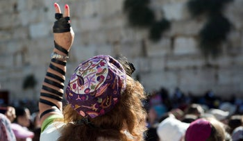 A woman wraps tefillin around herself at the Western Wall, Jerusalem.