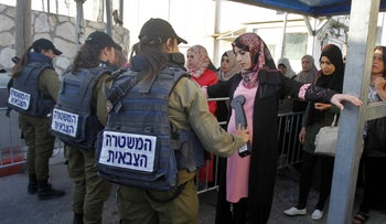 Palestinian woman being checked by Israeli Military Police at Jerusalem-Bethlehem checkpoint.