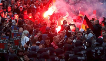 Right wing demonstrators light flares on August 27, 2018 in Chemnitz, eastern Germany, following the death of a 35-year-old German national