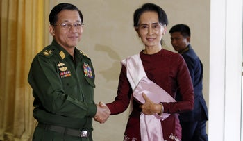 Myanmar's Commander-in-Chief Min Aung Hlaing (L) shakes hands with National League for Democracy (NLD) party leader Aung San Suu Kyi before their meeting in Naypyitaw.