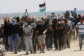 Palestinian protesters chant slogans while walk toward the fence during a protest at the Gaza Strip's border with Israel, Friday, May 11, 2018.