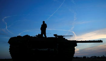 An Israeli soldier atop a tank looks at air force fighter jets circling overhead an Israeli Defence Forces (IDF) staging area in the northern Gaza border November 21, 2012.