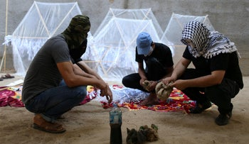 Palestinians preparing kites loaded with flammable material to be thrown at the Israeli side, near the Israel-Gaza border in the central Gaza Strip, June 4, 2018.