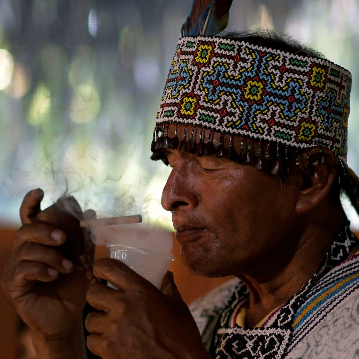 In this May 5, 2018 photo, Shaman Pablo Flores prepares to drink ayahuasca during a session in Nuevo Egipto, a remote village in the Peruvian Amazon.
