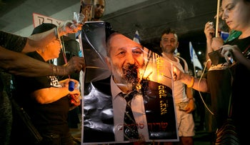 Demonstrators burn the picture of Israeli Interior Minister Aryeh Deri, on August 30, 2018.