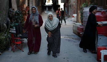 Palestinian residents walk on Lod street in the Palestinian Yarmouk refugee camp, Damascus, Syria, July 16, 2018.