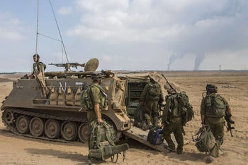 Israeli soldiers prepare for combat in the Gaza Strip at an army deployment along the border between Israel and the Hamas-controlled Palestinian territory on July 29, 2014.