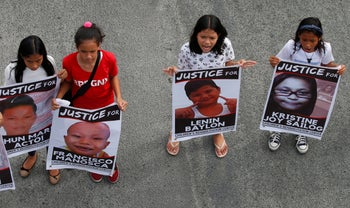 Protesters hold posters of young victims who died under President Rodrigo Duterte's so-called war on drugs during a rally coinciding with his third State of the Nation Address Monday, July 23, 2018, in Quezon city, northeast of Manila, Philippines.