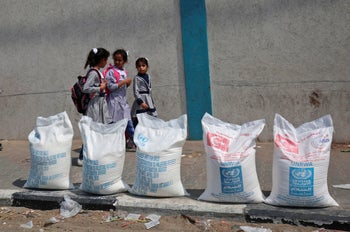 Palestinian school girls walk past sacks of flour outside a United Nations' compound at the Rafah refugee camp in the southern Gaza Strip on September 1, 2018.