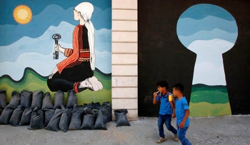Palestinian children walk past paintings depicting the 1948 'Naqba' or catastrophe, and the UNRWA site in the Fawwar Palestinian refugee camp, near Hebron, on September 2, 2018