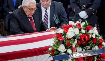 Former Secretary of State Henry Kissinger touches the casket of Sen. John McCain, R-Ariz., as he lies in state in the Rotunda of the U.S. Capitol, Friday, Aug. 31, 2018, in Washington