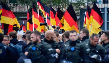FILE PHOTO: Far-right protesters wave German flags as they walk behind a barrage of riot police during a demonstration, Chemnitz, Germany, September 1, 2018.