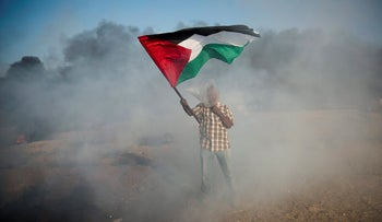 A Palestinian demonstrator protects himself from teargas during a protest at the Israel-Gaza border, August 10, 2018.