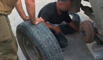 A Palestinian changes the tire of a military vehicle