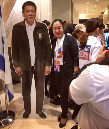 A Filipino is photographed with a cardboard picture of Duterte at the Ramada Hotel, September 2, 2018.