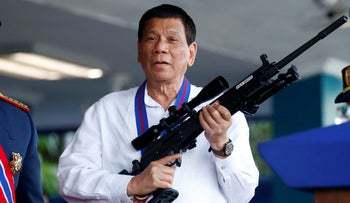 Philippine President Rodrigo Duterte, right holds an Israeli-made Galil rifle at a ceremony in Quezon city, April 19, 2018.