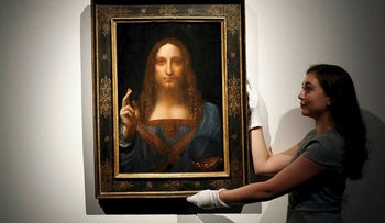 "In this Oct. 24, 2017 file photo, an employee poses with Leonardo da Vinci's ""Salvator Mundi"" on display at Christie's auction rooms in London"