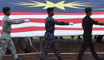 Malaysian Armed Forces personnel carry a huge national flag as they march during the National Day celebration parade in Putrajaya, on the outskirts of Kuala Lumpur on August 31, 2018