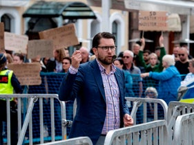 Protesters show placards as Sweden Democrats party leader Jimmie Akesson gives a speech to campaign in Malmo, southern Sweden, on August 31, 2018