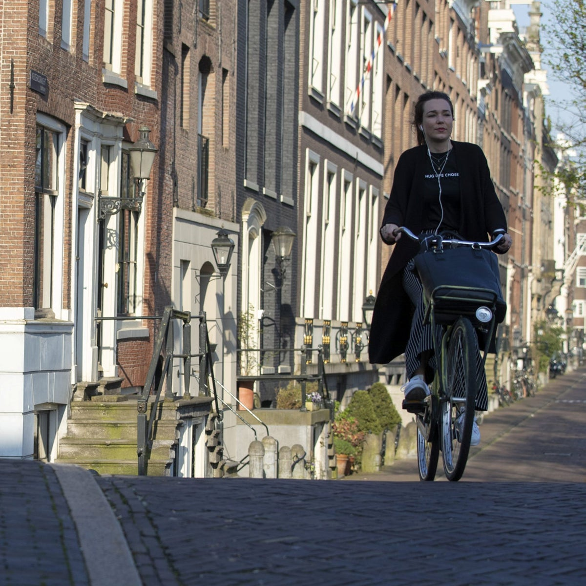 A cyclist travels towards a bridge on the corner of Reguliersgracht and Keizersgracht in Amsterdam, Netherlands.