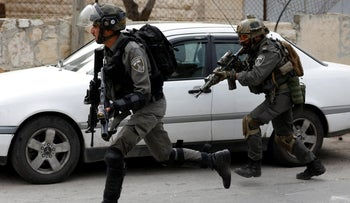 Israeli border police officers run toward Palestinians during a raid to al-Amari refugee camp, in Ramallah in the West Bank May 28, 2018.