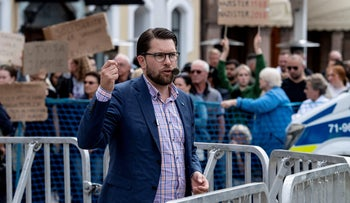 Protesters show placards as Sweden Democrats party leader Jimmie Akesson gives a speech in Malmo, Sweden, August 31, 2018.
