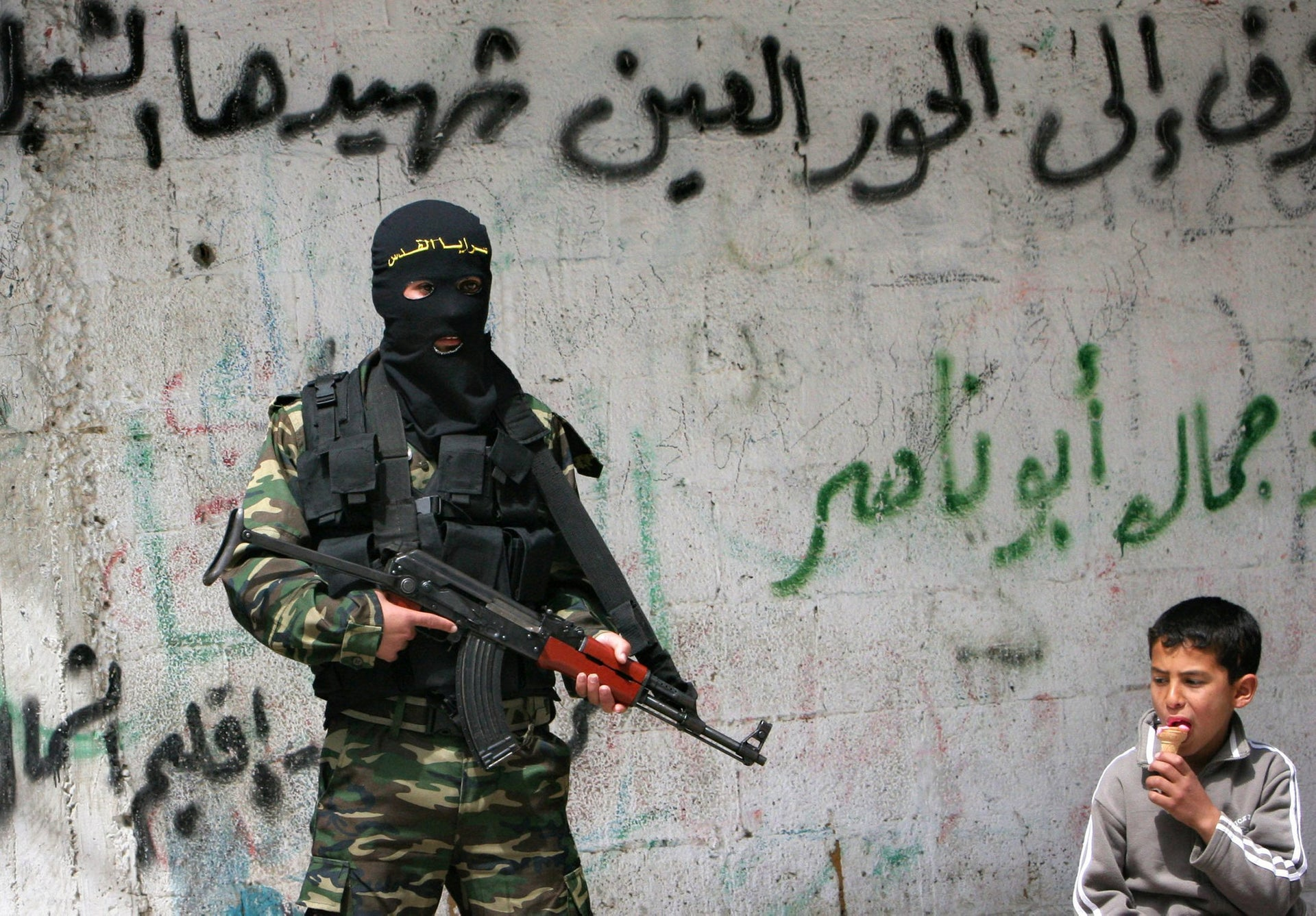 "A Palestinian boy eats ice cream next to a masked Islamic Jihad militant standing guard next to the house used by Hamas during recent clashes between Fatah and Hamas, in Beit Lahiya northern Gaza Strip, Thursday, March 22, 2007. A militant was killed during clashes between Fatah and Hamas militants in Beit Lahiya on Wednesday. Graffiti in Arabic reads ""We will send our martyr to paradise""."