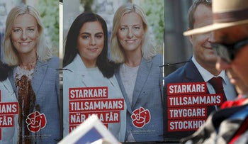 A man reads a newspaper next to Sweden's Social Democratic party election campaign posters in Stockholm, Sweden September 6, 2018