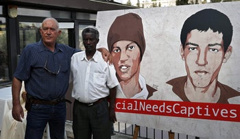 File photo: Shabaan al-Sayed (L) and Ayeli Mengistu (R) next to a poster depicting their sons, held by Hamas in Gaza, after a press conference calling for their release, September 6, 2018.
