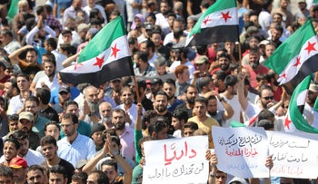 Syrian protesters wave their national flag as they demonstrate against the regime and its ally Russia, in the rebel-held city of Idlib on September 7, 2018.