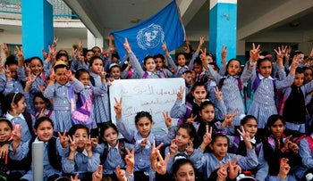Palestinian children chant slogans and raise the victory gesture during a protest at a United Nations Relief and Works Agency (UNRWA) school, financed by US aid, in the Arroub refugee camp near Hebron in the occupied West Bank on September 5, 2018.