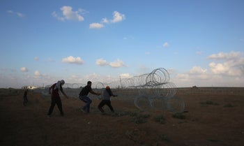 Protesters pull out a part of barbed wire of the fence of the Gaza Strip border with Israel, during a protest east of Gaza City, September 7, 2018.