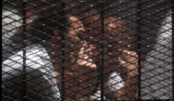 Egyptian photojournalist Mahmoud Abu Zeid, also known as Shawkan, smokes cigarette behind a fence during his trial in Cairo, Egypt, September 8, 2018.
