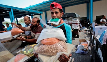 Palestinian men collect aid food at a United Nations' compound in the Rafah refugee camp in the southern Gaza Strip on September 1, 2018.