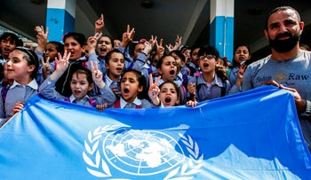 Palestinian children chant slogans and raise the victory gesture over a UN flag during a protest at a United Nations Relief and Works Agency (UNRWA) school, financed by US aid, in the Arroub refugee camp near Hebron in the West Bank on September 5, 2018