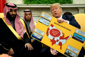 FILE PHOTO: U.S. President Donald Trump holds a chart of military hardware sales as he welcomes Saudi Arabia's Crown Prince Mohammed bin Salman in the Oval Office at the White House in Washington, U.S. March 20, 2018.