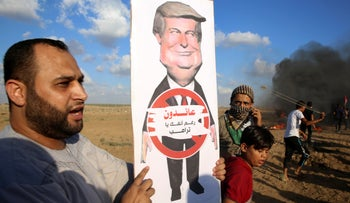 "A Palestinian protester holding a poster of President Donald Trump near the Gaza Strip border, September 7, 2018. The poster's message says: ""We are returning in spite of you, Trump."""