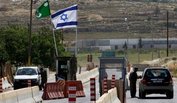 Illustrative photo of Israeli border police officers and Palestinian drivers at a checkpoint near Ramallah.