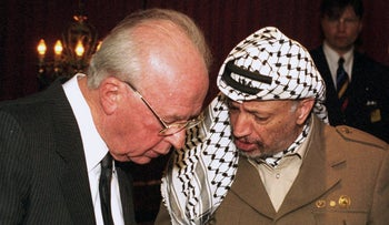 Israel's Prime Minister Yitchak Rabin and PLO Chairman Yasser Arafat conferring after being awarded, together with Foreign Minister Shimon Peres, the 1994 Nobel Peace Prize in Oslo