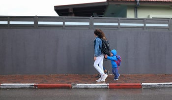 A woman walks with her children in Ashdod, Israel, 2017.