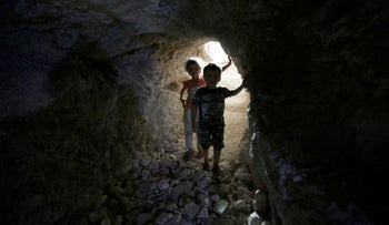 FILE PHOTO: Children walk in a makeshift shelter in an underground cave in Idlib, Syria September 3, 2018