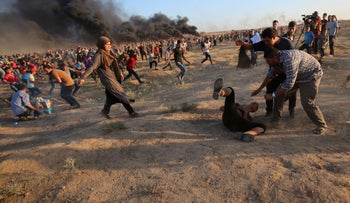 Palestinians help an injured protester during a demonstration along the Israeli fence east of Gaza City on September 14, 2018.