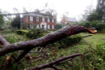 Toppled trees land in the yard and on a home in Wilmington, N.C., after Hurricane Florence made landfall Friday, Sept. 14, 2018.