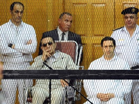 Former Egyptian President Hosni Mubarak, seated center left, and his two sons, Gamal Mubarak, left, and Alaa Mubarak attend a hearing in a courtroom in Cairo, Egypt, in this Sept. 14, 2013 file photo.